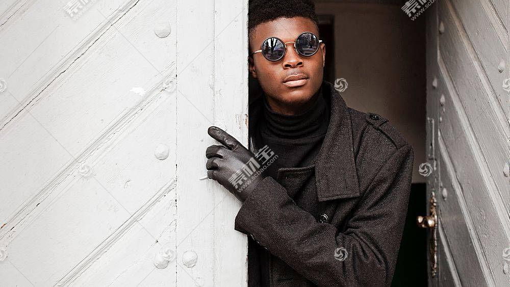穿黑大衣打开门的黑人男子