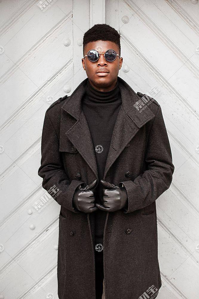 穿黑大衣戴手套的黑人男子