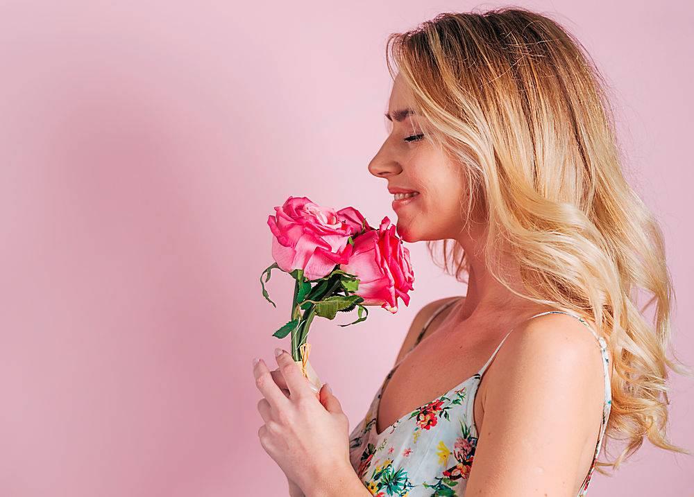 粉色背景下手持玫瑰花的金发年轻女子微笑的_386573801