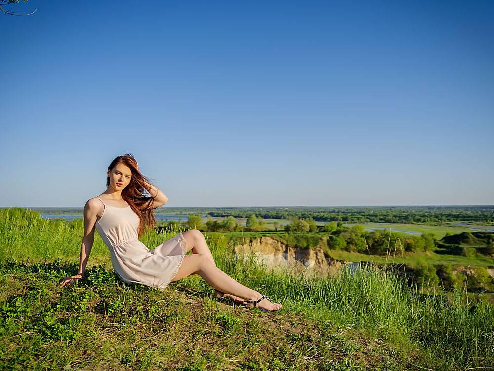 坐在户外悬崖边的年轻女子穿着白色连衣裙_1196116601