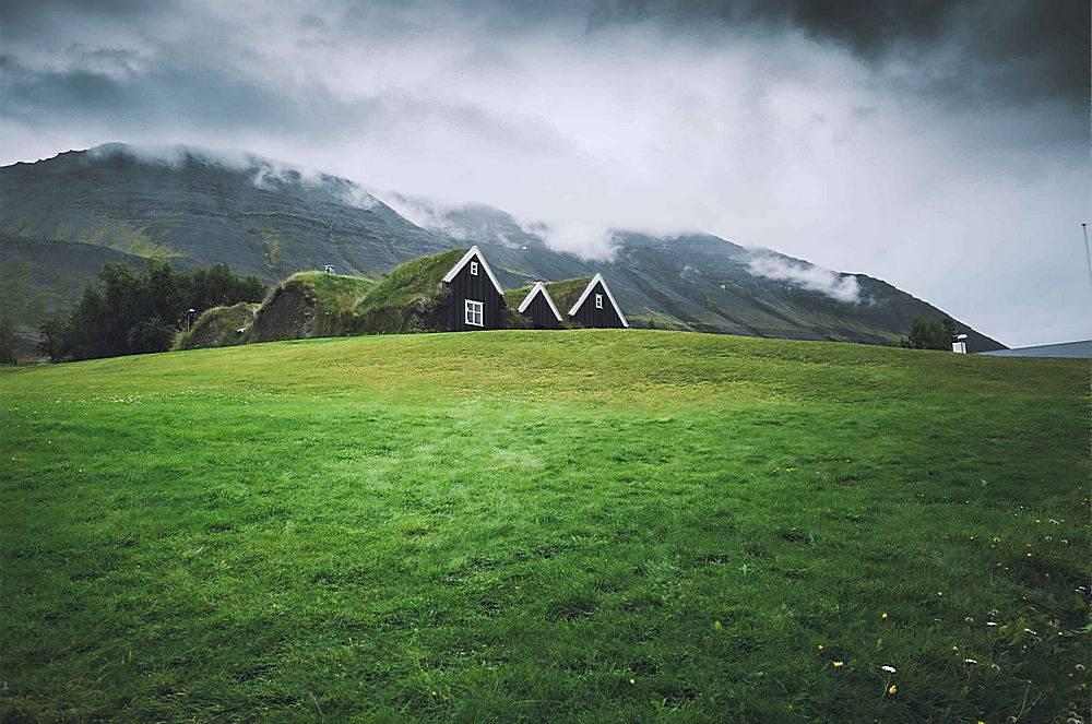 天空暗淡的绿色田野里的小房子_755392901