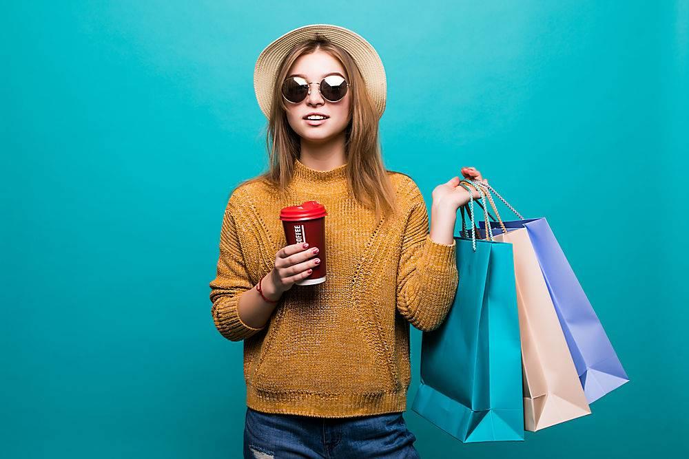 一位年轻女子拿着咖啡带走拿着购物袋在_907681501