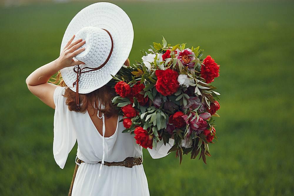 一位身着优雅服饰的女子站在夏日的田野上_934375501