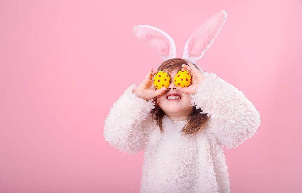 一幅长着兔子耳朵和复活节彩蛋的小女孩的肖_943449601