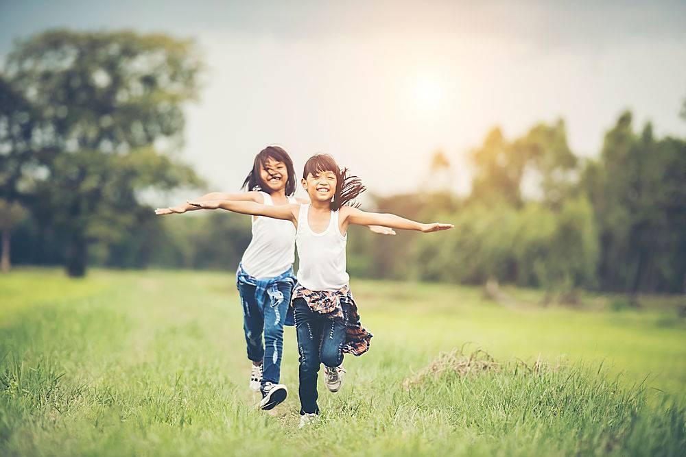 两个可爱的小女孩正在绿色的草地上奔跑最_288728701
