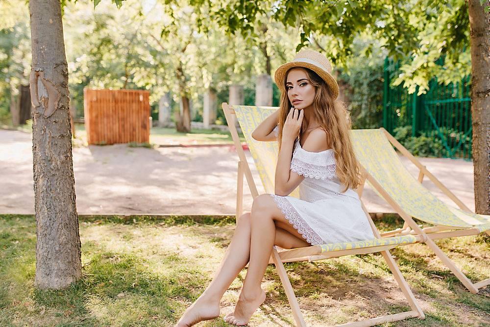 优雅的赤脚女士戴着草帽坐在长沙发上脸_1048511501