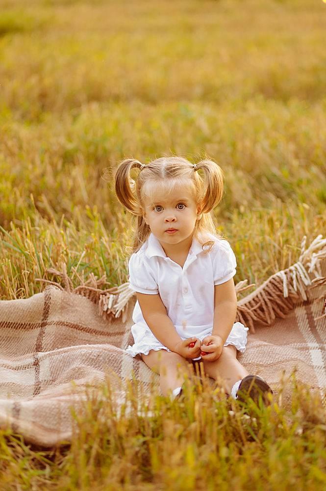 穿着白色连衣裙的可爱小孩子在绿色的田野上_1103374701
