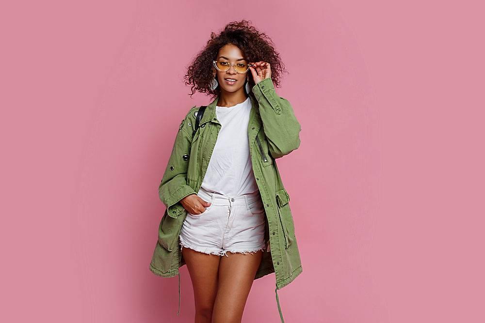 穿着绿色夹克的漂亮时髦黑人女孩在粉色背景_911612301