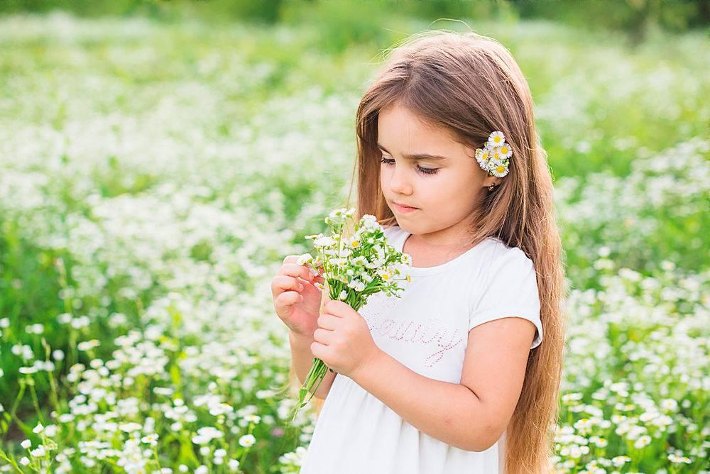 留着长发的女孩看着她在田野里采集的白花_309011201