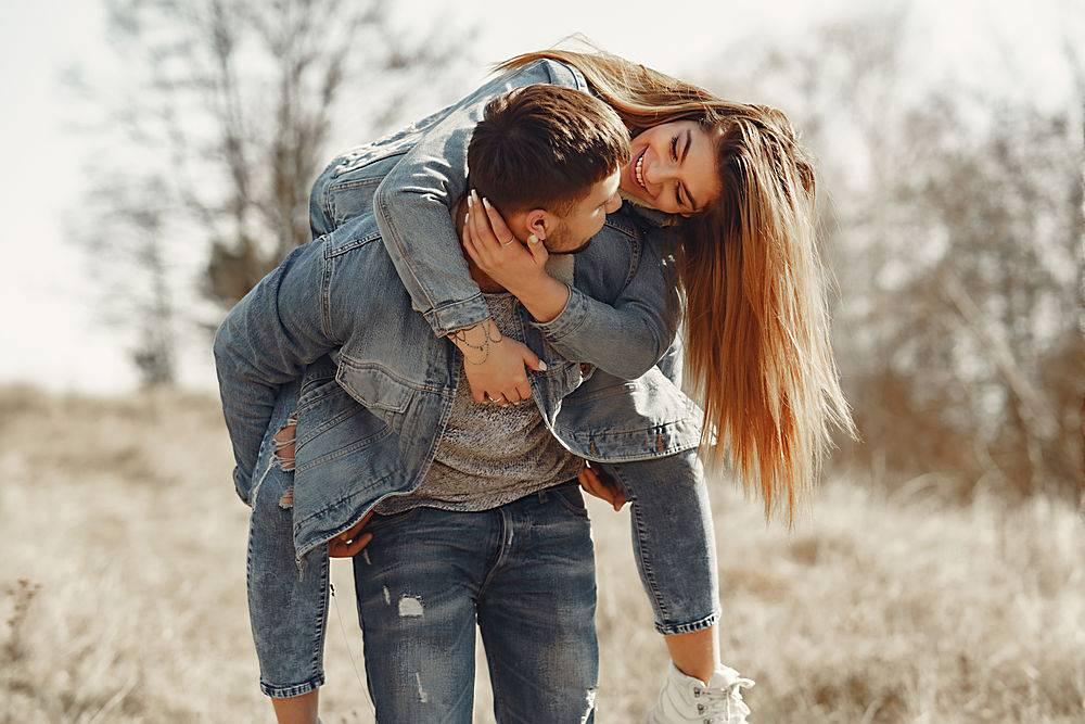 春天田野里一对穿着牛仔裤衣服的可爱情侣_771053601