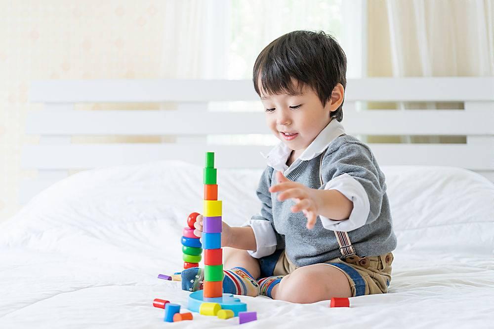 小男孩快乐地玩着五颜六色的木质学习玩具_538899701