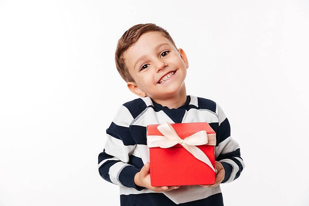 一个拿着礼品盒的可爱的小孩子的肖像_733691601