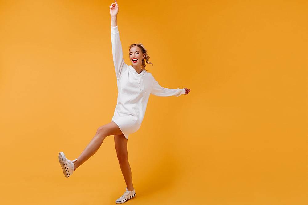活潑的女士修長的腿在橙色的房間里移動_1230523801
