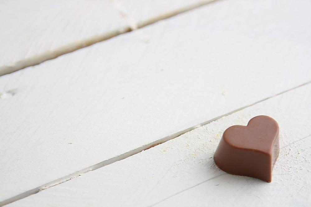 白色木桌上心形巧克力糖的特写镜头_1159969601