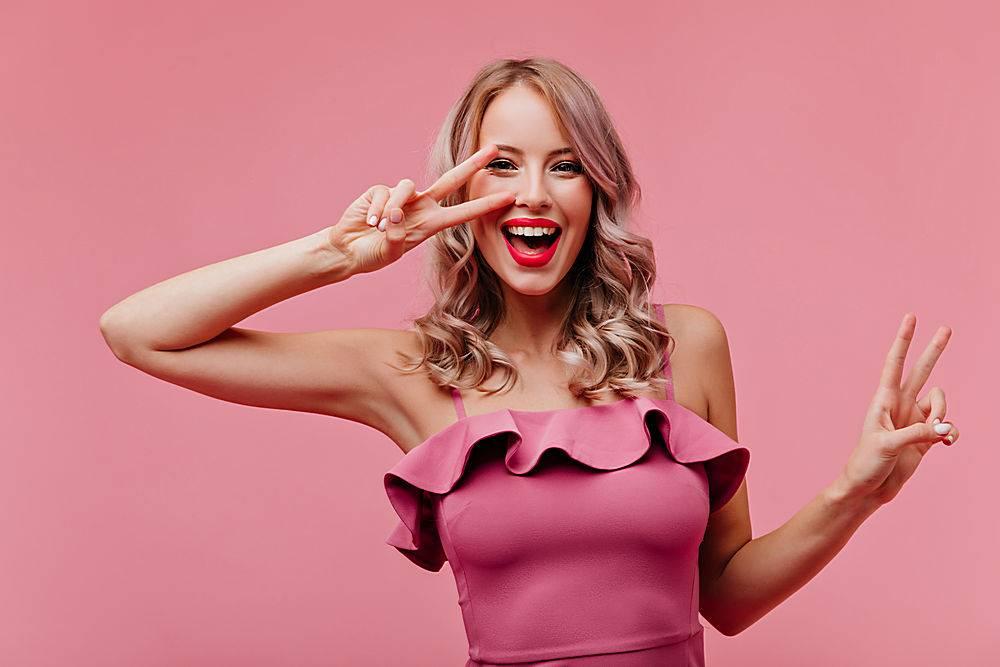 满意的女士留着浪漫的发型在粉色墙上大_1230538301