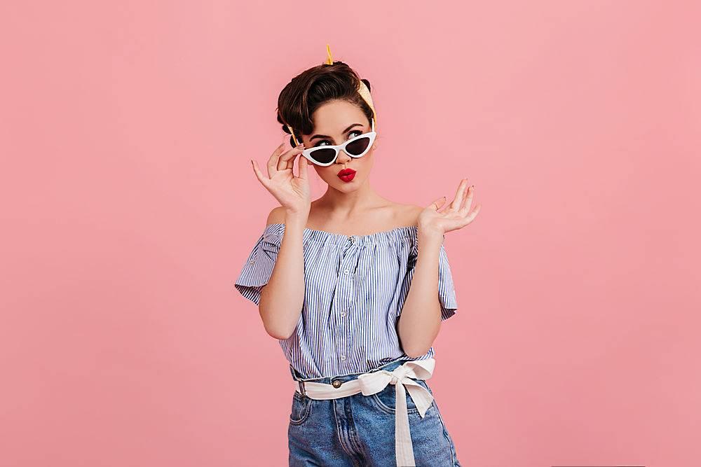 戴著墨鏡的沉思的美女站在粉色的背景上攝_1243013301
