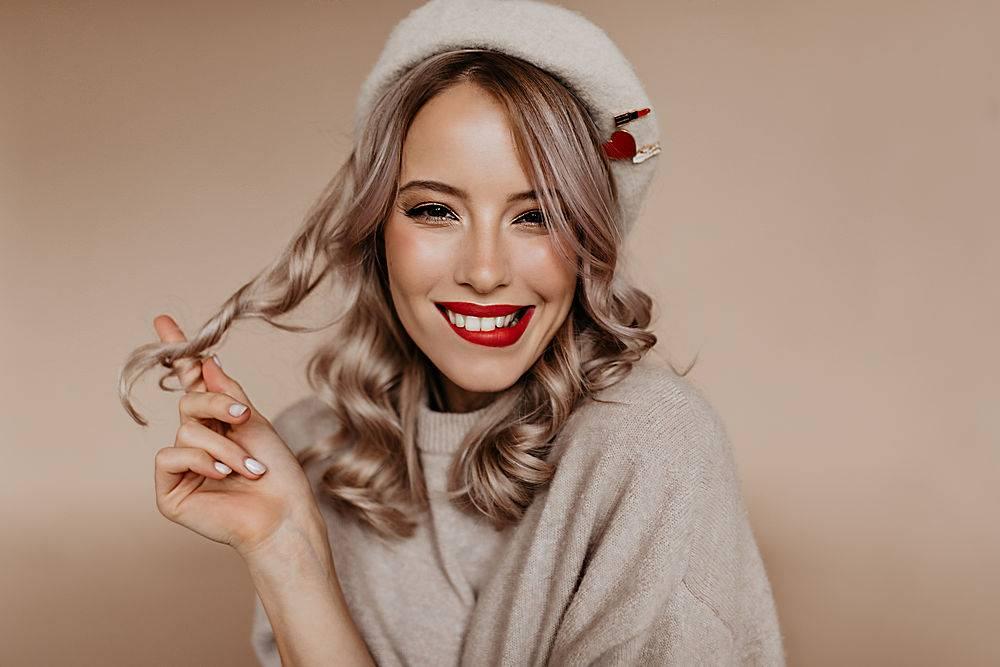 可爱的法国女人在棕色墙上玩弄她的卷发_1230528301