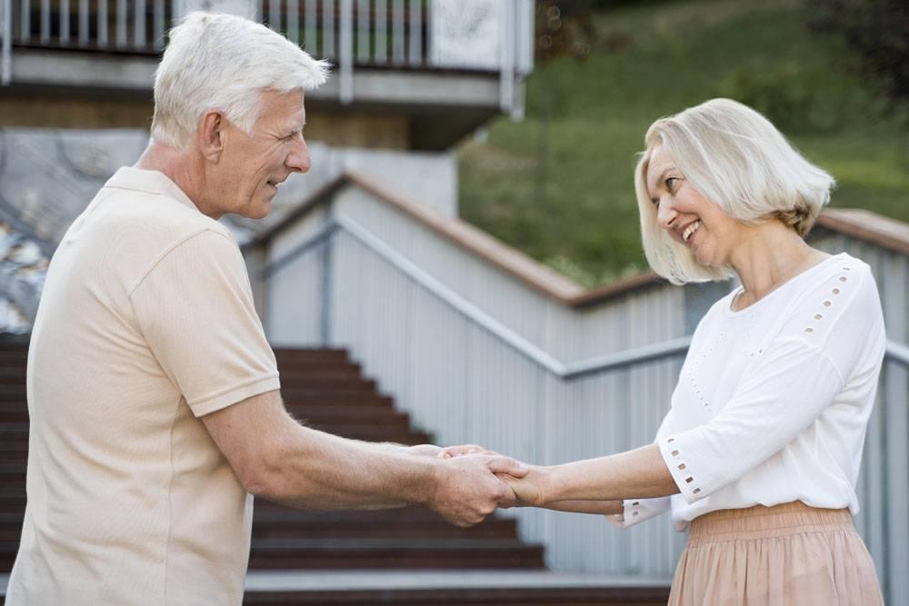 浪漫相爱的老年夫妇在户外手牵手的侧观_980565501