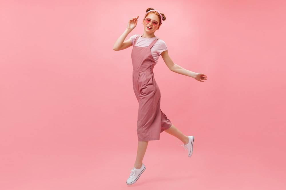 身穿粉色连体裤T恤和时髦眼镜的活跃女性_12677959