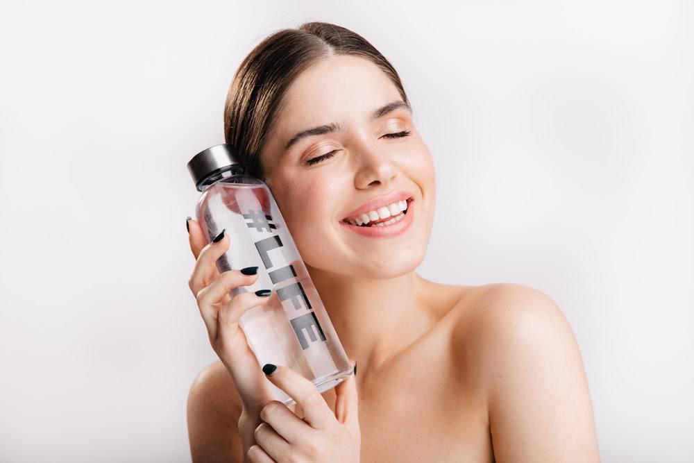 可爱的素颜女孩在隔壁上摆着瓶装水的姿势_12607341