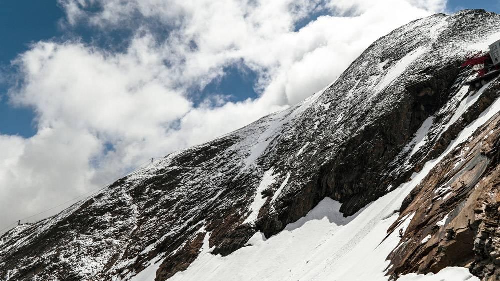 多云天空下积雪覆盖的山区风景的美丽风景_1321079101