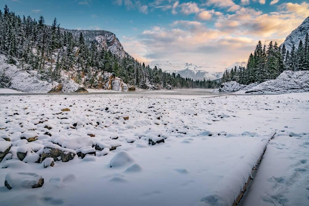多云天空下群山环绕的森林里美丽的冬季风景_928293501