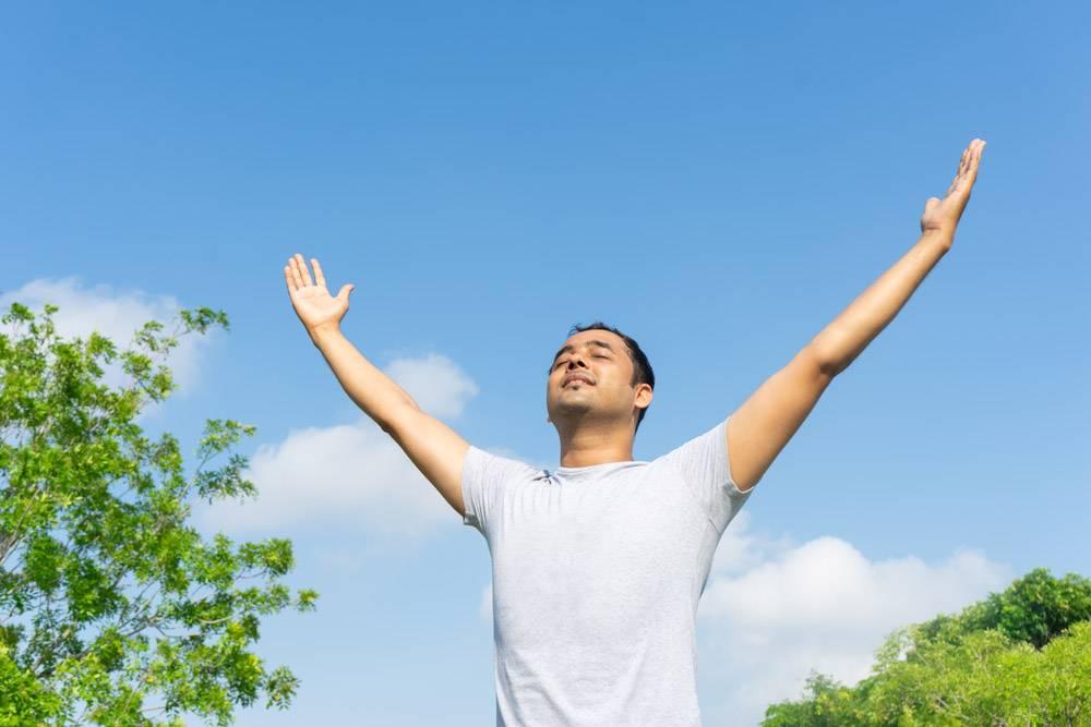一名印度男子在蓝天绿枝的户外聚精会神举手_2538597
