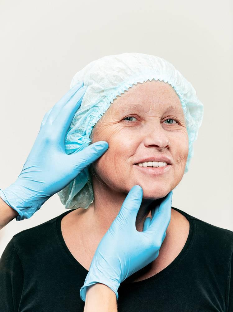 外科医生在整形手术前对中年女性进行皮肤检_7308097