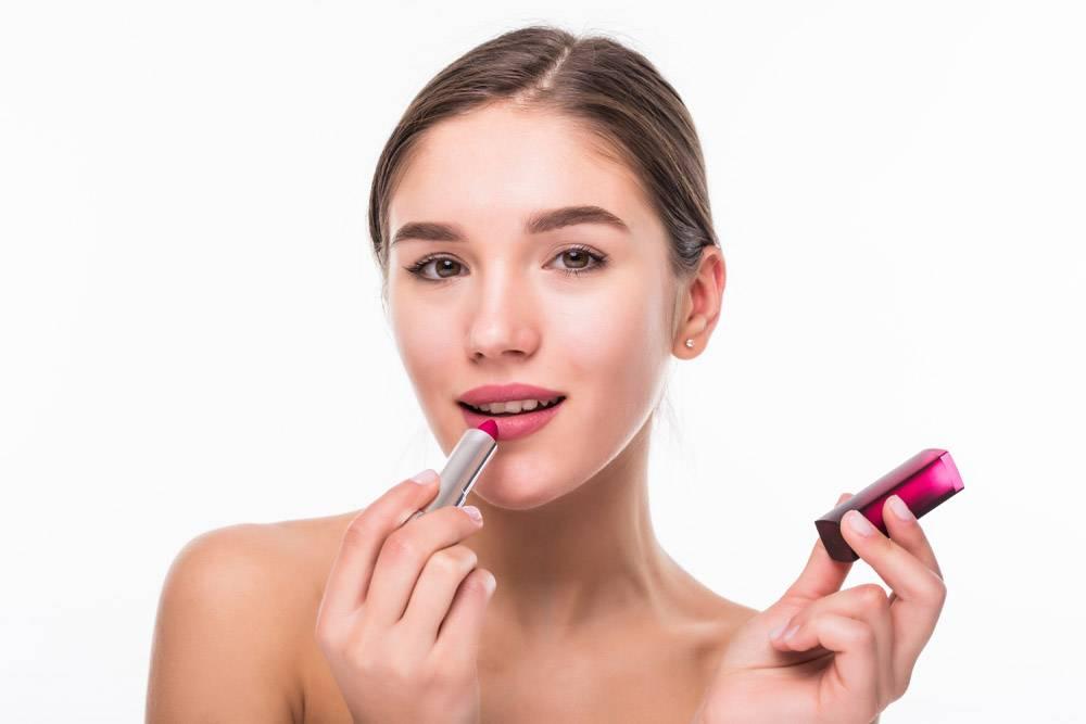 美丽的年轻女子将唇膏涂在隔绝在白色墙壁上_8472859