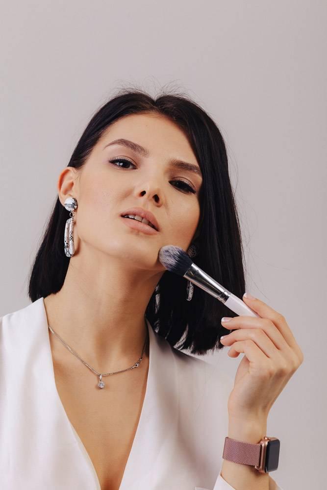 漂亮的年轻女生意人用化妆刷在朴素的背景_9072614