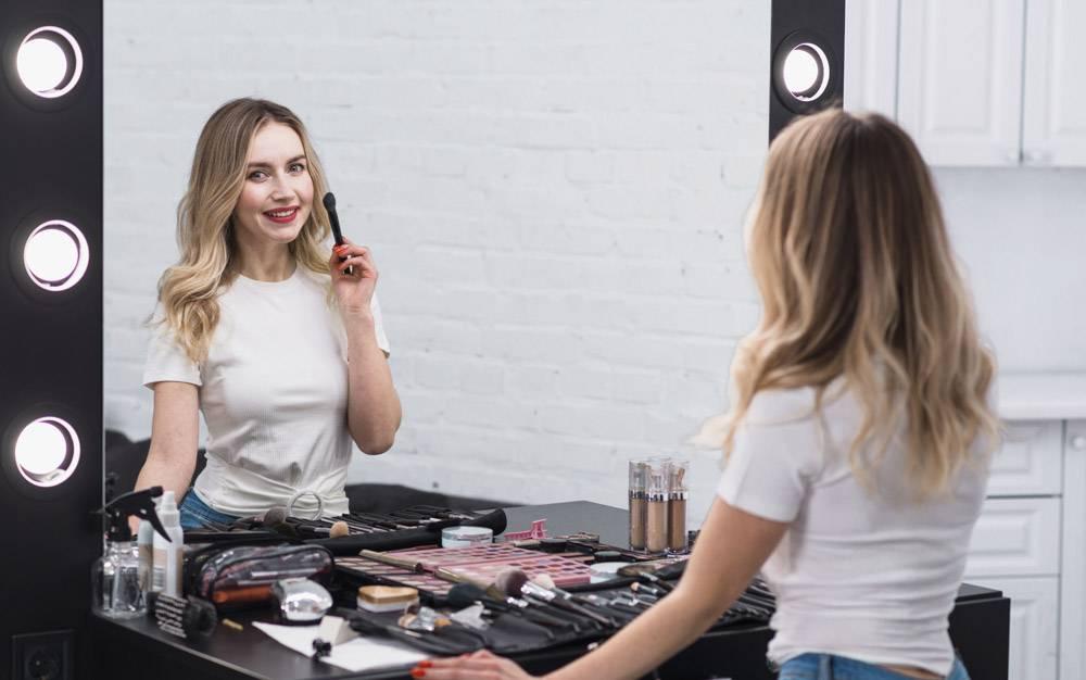 拿着化妆刷站在镜子前的女人_4332610