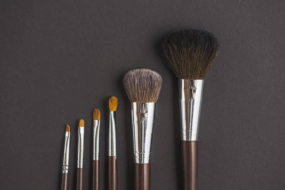 黑色背景上的一排化妆刷_3105817
