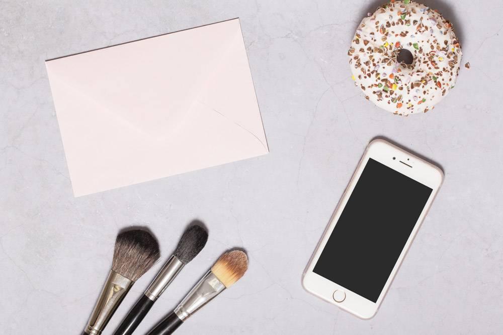 画笔和纸附近的甜甜圈和智能手机_1597977