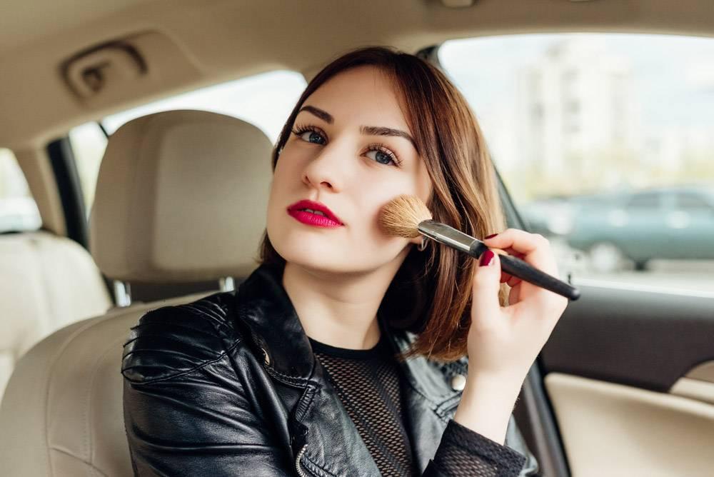 停在车流中的年轻女孩在修饰自己的妆容_2455285