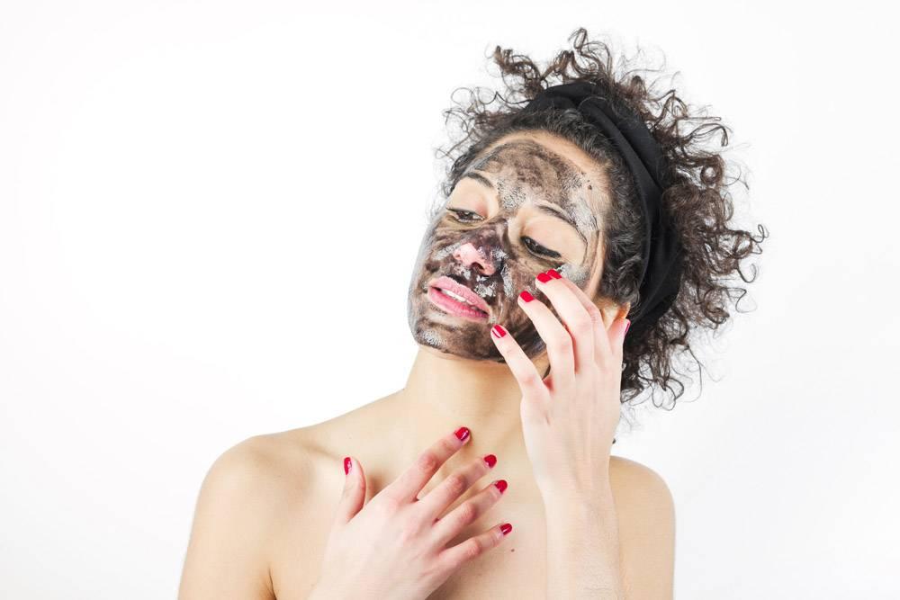 一名年轻女子在白色背景下戴上黑色口罩的特_3186744