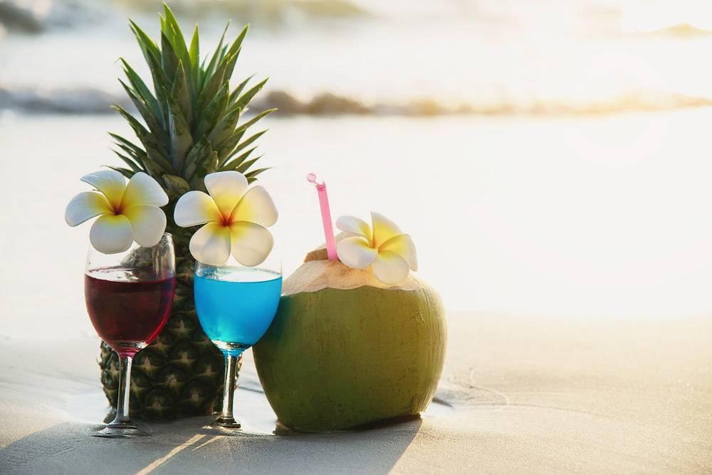 在干净的沙滩上配椰子和菠萝的鸡尾酒杯在_5072123