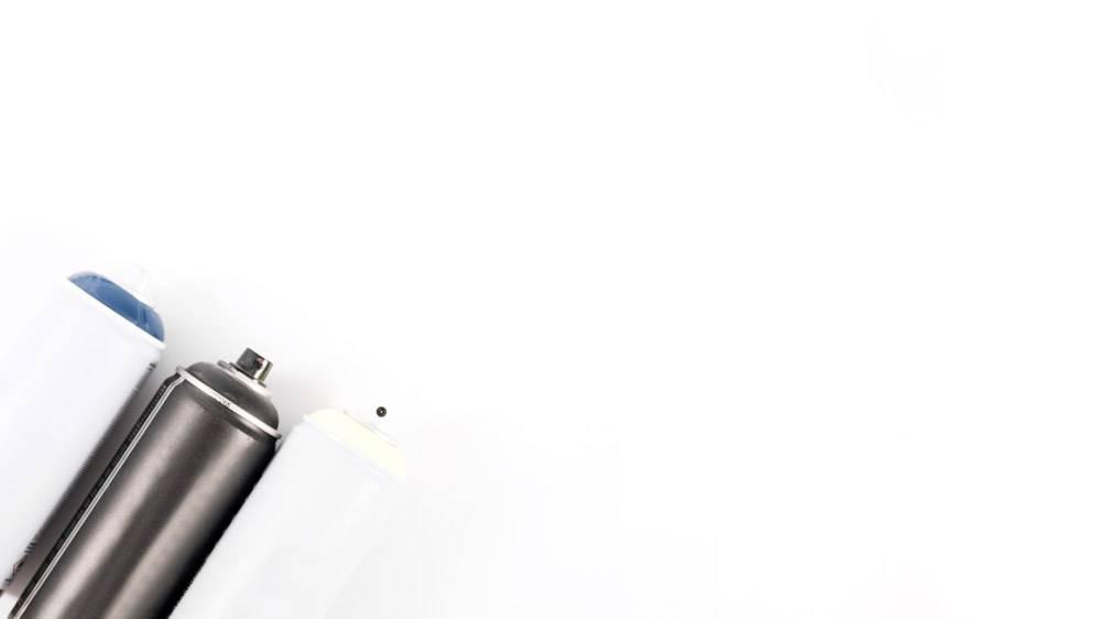 隔绝在白色背景上的排成一排的金属喷雾罐的_2559366
