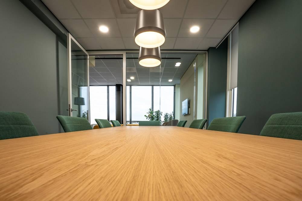 房间里有一张棕色的桌子周围有绿色的椅子_10291792