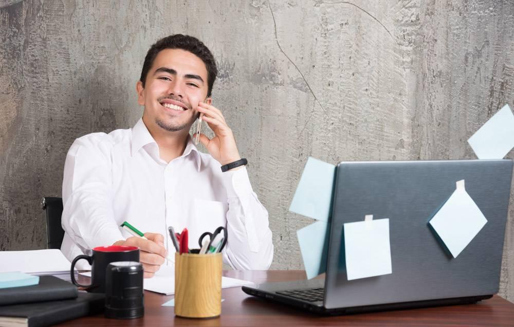快乐的商人在办公桌边谈生意做笔记_11799953