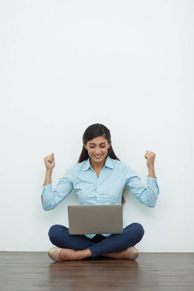 快乐的年轻女子在地板上用笔记本电脑工作_992716