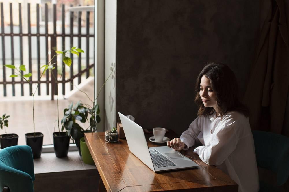咖啡厅里的一名妇女正在用笔记本电脑工作_6154183