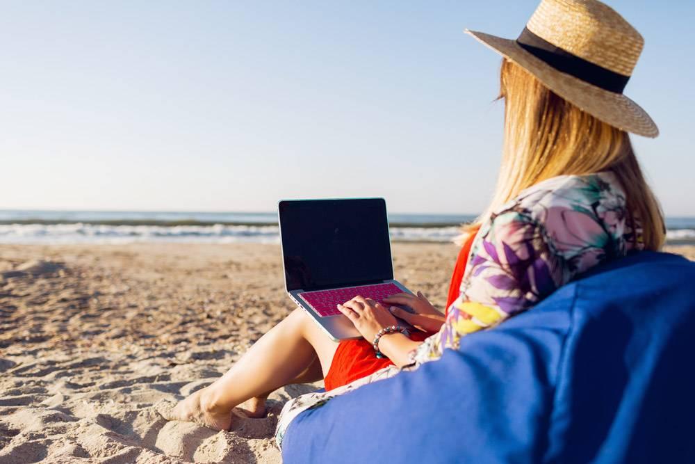 美丽的年轻女子在热带海滩上用笔记本电脑工_9686726