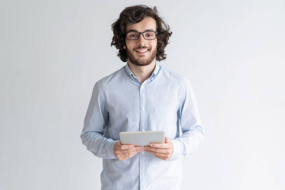 微笑的年轻人站着拿着平板电脑_4167188