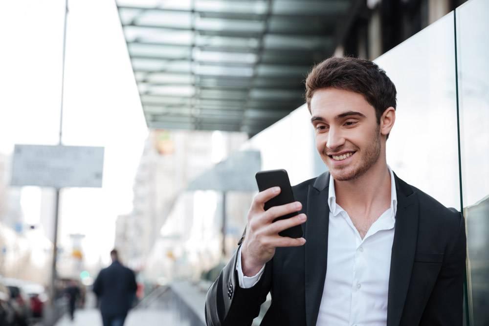 微笑的年轻商人走在商业中心附近_8196258