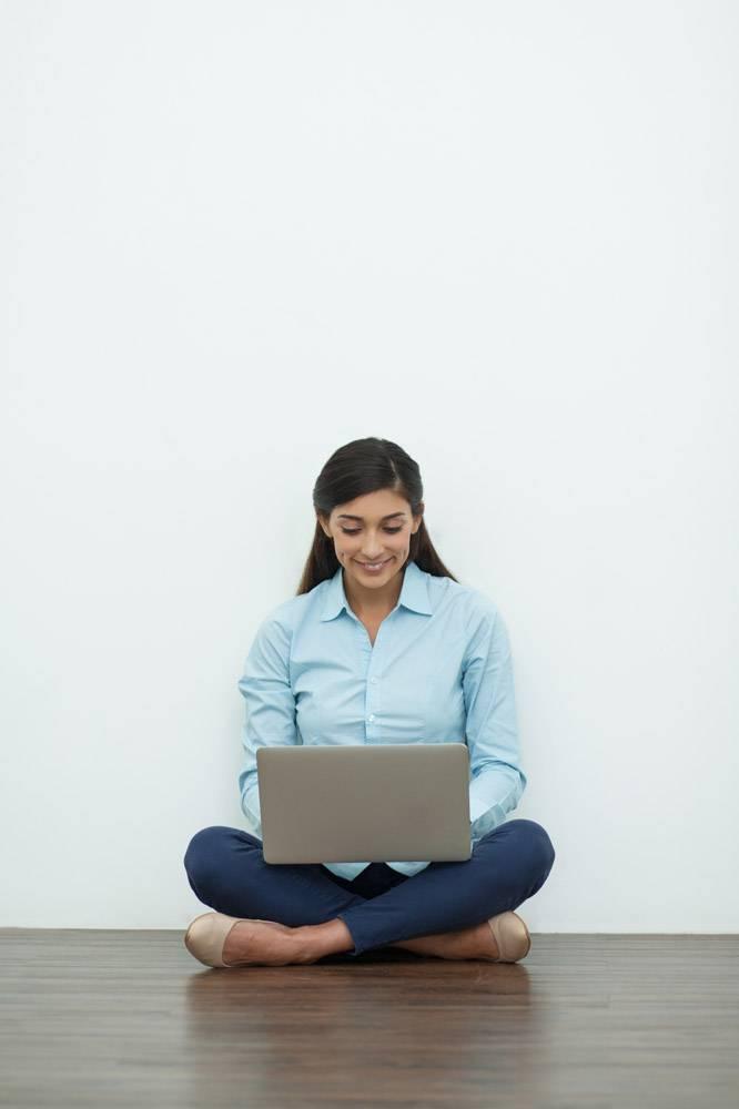 微笑的年轻女子在地板上用笔记本电脑工作_993032