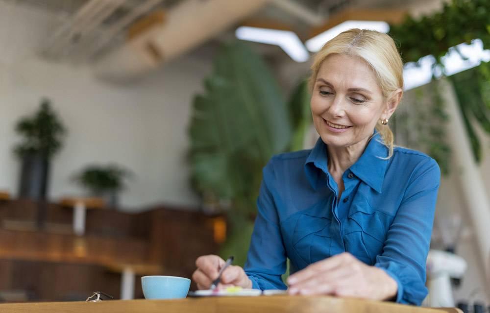 微笑的年长女商人在用餐时写议事日程_9943347