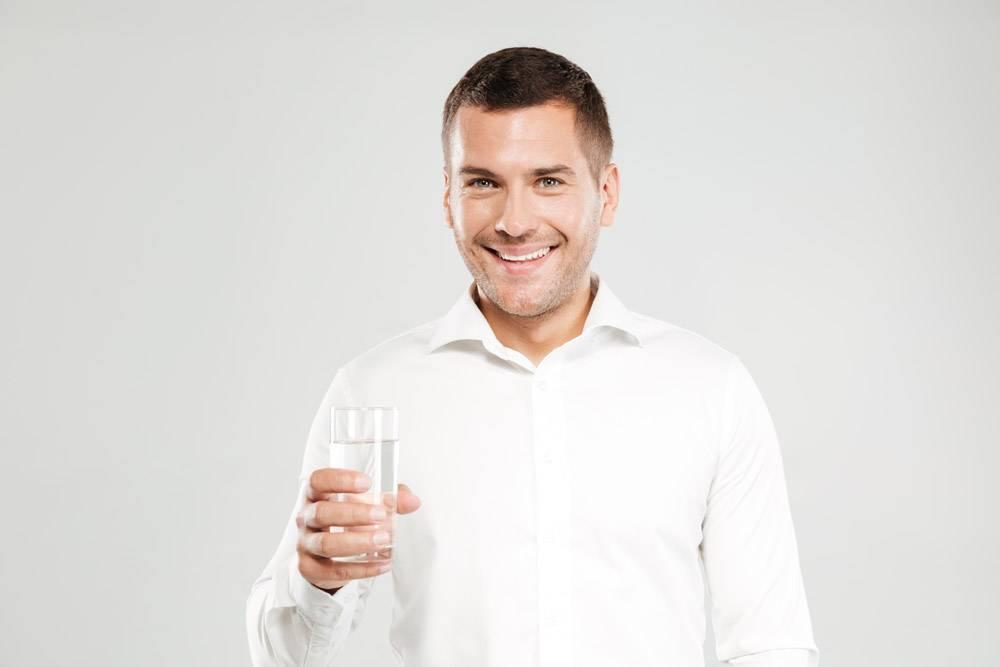 快乐的年轻人拿着装满水的玻璃杯_7338587