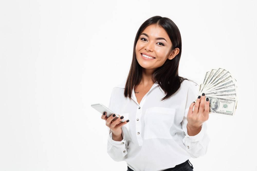 快乐的亚洲年轻女子用手机拿着钱_7380239