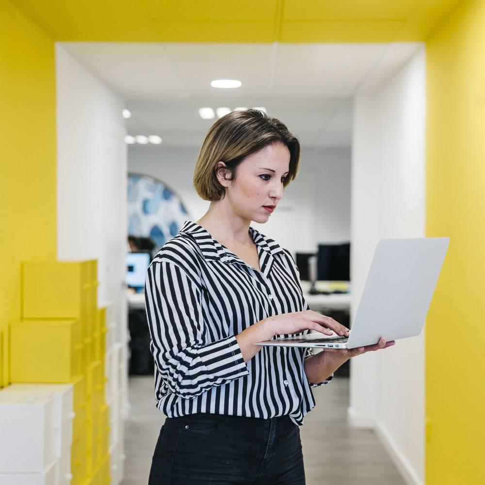 年轻女子在办公室大厅使用笔记本电脑_2088974
