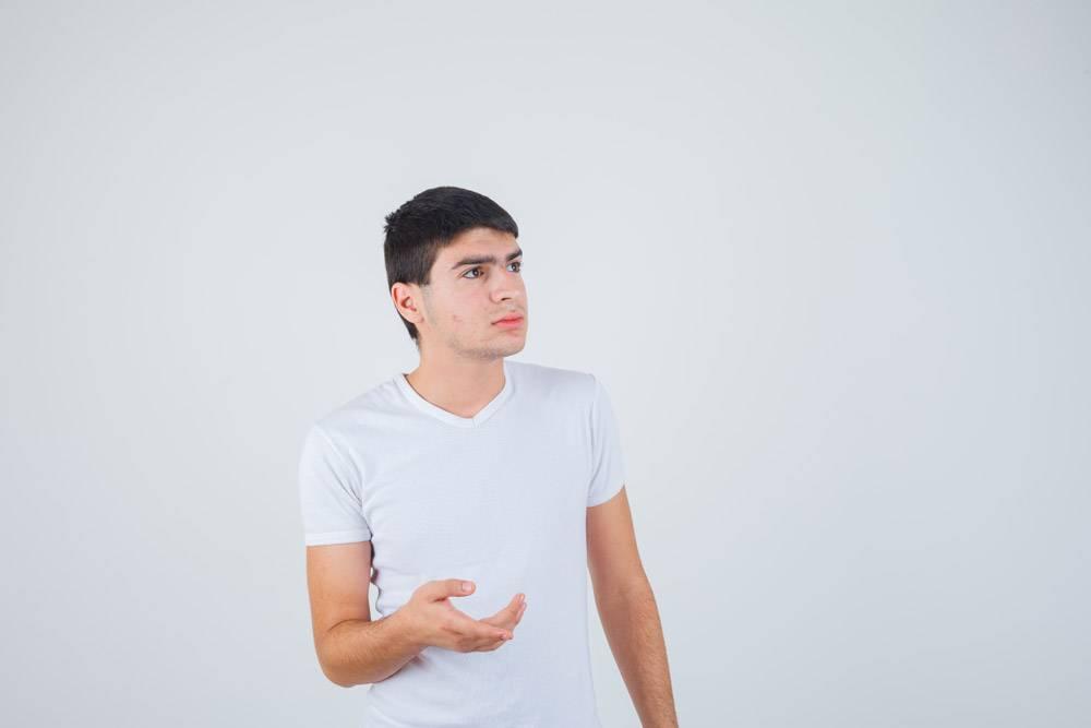 年轻男性穿着t恤伸出手做询问的手势看起_13462766